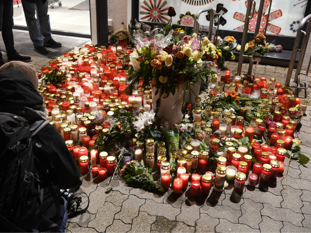 People leave candles and flowers outside a grocery store where a 15-year-old girl was stabbed to death by her Afghan ex-boyfriend on January 2, 2018 in the western German town of Kandel. / AFP PHOTO / dpa / Uli Deck / Germany OUT (Photo credit should read ULI DECK/AFP/Getty Images)