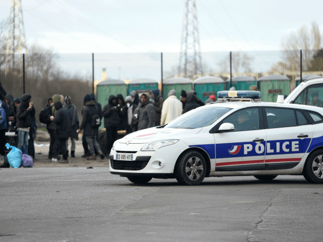 A police vehicle passes by people gathering in Calais, northern France, on February 2, 2018, a day after a large brawl between a hundred migrants resulted in several injuries. Four migrants were in critical condition after being shot and more than a dozen others were injured, some seriously, during clashes …
