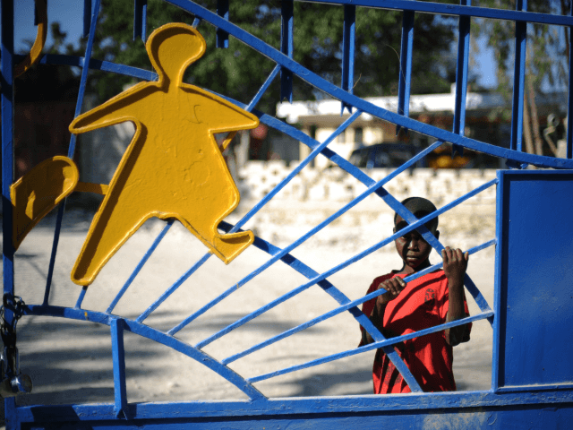 A child waits at the gates of the SOS Children's Village in Croix des Bouquets, outside of Port-au-Prince on February 1, 2010. Ten members of a US Christian group charged with child-trafficking in Haiti could be tried in the United States and will possibly go before a judge later today, …