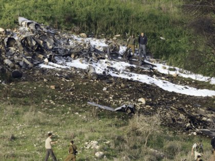 "Israeli security stands around the wreckage of an F-16 that crashed in northern Israel, near kibbutz of Harduf, Saturday, Feb. 10, 2018. The Israeli military shot down an Iranian drone it said infiltrated the country early Saturday before launching a ""large-scale attack"" on at least a dozen Iranian and Syrian …"