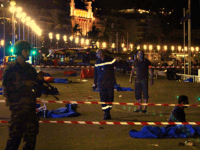 Soldiers, police officers and firefighters walk near dead bodies covered with a blue sheets on the Promenade des Anglais seafront in the French Riviera town of Nice on July 15, 2016, after a truck drove into a crowd watching a fireworks display. At least 75 people were killed when a …