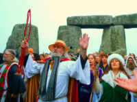 SALISBURY, ENGLAND - DECEMBER 22: Druids, pagans and revellers gather in the centre of Stonehenge, hoping to see the sun rise, as they take part in a winter solstice ceremony at the ancient neolithic monument of Stonehenge near Amesbury on December 22, 2017 in Wiltshire, England. Despite a forecast for cloud and rain, a large crowd gathered at the famous historic stone circle, a UNESCO listed ancient monument, to celebrate the sunrise closest to the Winter Solstice, the shortest day of the year. The event is claimed to be more important in the pagan calendar than the summer solstice, because it marks the 're-birth' of the Sun for the New Year. (Photo by Matt Cardy/Getty Images)