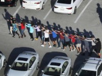 People are brought out of the Marjory Stoneman Douglas High School after a shooting at the school that reportedly killed and injured multiple people on February 14, 2018 in Parkland, Florida. Numerous law enforcement officials continue to investigate the scene. (Photo by Joe Raedle/Getty Images)
