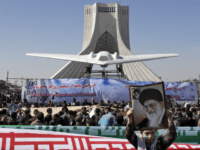 A model of a U.S. RQ-170 Sentinel, captured by Iran in December near the border with Afghanistan, is displayed in front of the Azadi (freedom) tower, as a boy holds a poster showing supreme leader Ayatollah Ali Khamenei, at a rally marking the 33rd anniversary of the Islamic Revolution that toppled the country's pro-Western monarchy and brought Islamic clerics to power, Tehran, Iran, Saturday, Feb. 11, 2012. (AP Photo/Vahid Salemi)