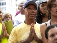 """Russell Simmons, co-founder of Def Jam records, participates in a session of yoga, led by yoga instructor Seane Corne, in collaboration with the """"Occupy Wall Street"""" protests in Zuccotti Park in New York, on Monday, Oct. 10, 2011. (AP Photo/Andrew Burton)"""