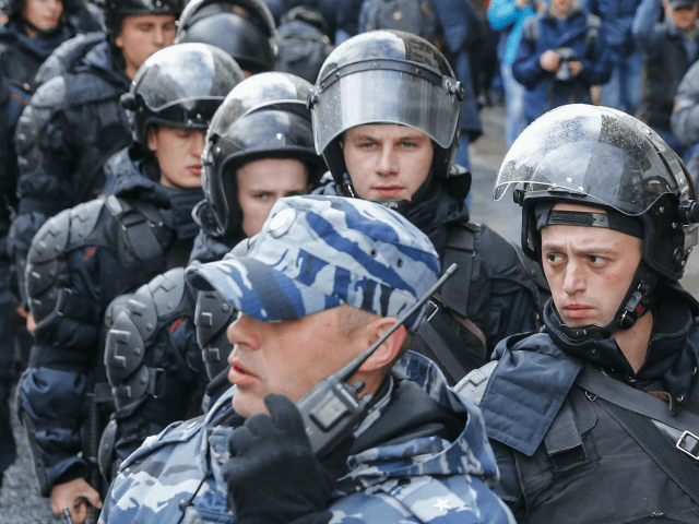 Riot police follow demonstrators walking along Tverskaya street during an unauthorized anti-Kremlin rally called by opposition leader Alexei Navalny, who is serving a 20-day jail sentence, in downtown Moscow on October 7, 2017, President Vladimir Putin's 65th birthday. / AFP PHOTO / Maxim ZMEYEV (Photo credit should read MAXIM ZMEYEV/AFP/Getty …