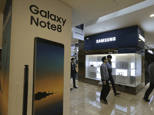 People pass by an advertisement of Samsung Electronics' Galaxy Note 8 smartphone at its shop in Seoul, South Korea, Wednesday, Jan. 31, 2018. Samsung Electronics has reported a surge in quarterly earnings thanks to its record-breaking chip business. (AP Photo/Ahn Young-joon)