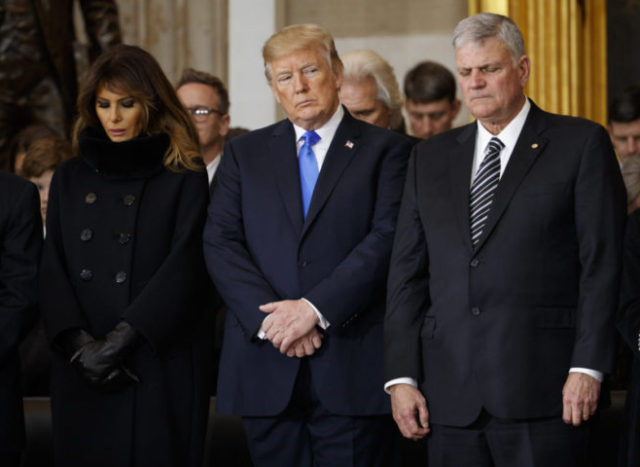 First lady Melania Trump, President Donald Trump, and Franklin Graham pray during a ceremony honoring Reverend Billy Graham in the Rotunda of the U.S. Capitol building, Wednesday, Feb. 28, 2018, in Washington. (AP Photo/Evan Vucci)
