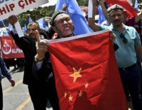 Turkish nationalists holds placards reading 'Turkey save your Brother-China get out from east Turkhistan' and hold a Chinese flag, during a protest to denounce China's treatment of ethnic Uighur Muslims, in front of the Chinese consulate in Istanbul, on July 5, 2015. Turkish media reported restrictions on Muslim Uighurs worshipping …