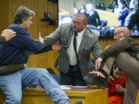 Randall Margraves, father of three victims of Larry Nassar , left, lunges at Nassar, bottom right, Friday, Feb. 2, 2018, in Eaton County Circuit Court in Charlotte, Mich. The incident came during the third and final sentencing hearing for Nassar on sexual abuse charges. The charges in this case focus …