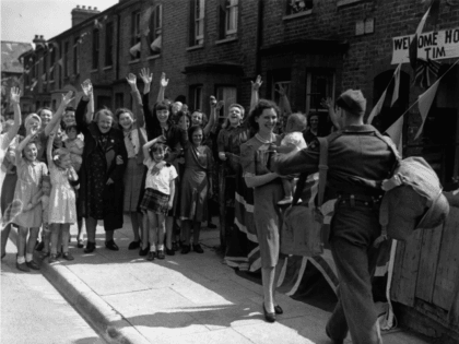 1944: Neighbours wave and cheer as they watch a young soldier being welcomed home from the Second World War by his wife and baby.