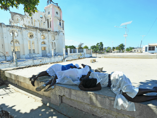 Women lay prostrate in prayer for victims of the January 12, 2010 Haiti earthquake near the destroyed Cathedral of Port-au-Prince on January 12, 2013. Three years after a massive earthquake ravaged Haiti, President Michel Martelly said the country was slowly rebuilding, despite the ongoing day-to-day misery of many survivors. An estimated 250,000 people were killed in the January 12, 2010 earthquake. Hundreds of thousands are still living rough in squalid makeshift camps, and they now face rampant crime, a cholera outbreak and the occasional hurricane.during memorial day in honor of the victims of the last quake of January 12 2013 in Haiti.People put photo of parent and friend victims of the quake.