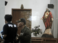 In this image shot through a glass window, police investigators examine the interior of St. Lidwina Church that was damaged following an attack in Sleman, Yogyakarta province, Indonesia, Sunday, Feb. 11, 2018. Police shot a sword-wielding man who attack the church during a mass, injuring a number of people including …
