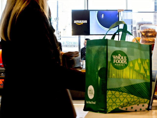 A customer stands at a coffee bar in front of an Amazon.com Inc. Pop-Up store inside the Lakeview Whole Foods Market Inc. store in Chicago, Illinois, U.S., on Monday, Nov. 20, 2017. Amazon.com Inc. is betting that people shopping for discounted organic Thanksgiving turkeys at Whole Foods this week may decide to pick up an Echo digital assistant as well. The company is using the holiday moment and its broader brick-and-mortar presence to further a lead in the emerging market for voice-activated smart home speakers. Photographer: Daniel Acker/Bloomberg via Getty Images
