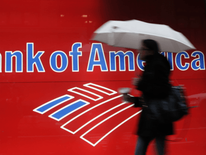 In this Dec. 7, 2011 photo, a woman passes a Bank of America office branch, in New York. Bank of America said Jan. 19, 2012, it made $2 billion in the last three months of 2011 from selling its stake in a Chinese bank and selling debt. That offset losses …