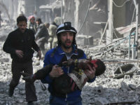 A Syrian civil defence member carries an injured child rescued from between the rubble of buildings following government bombing in the rebel-held town of Hamouria, in the besieged Eastern Ghouta region on the outskirts of the capital Damascus, on February 19, 2018. Heavy Syrian bombardment killed 44 civilians in rebel-held Eastern Ghouta, as regime forces appeared to prepare for an imminent ground assault. / AFP PHOTO / ABDULMONAM EASSA (Photo credit should read ABDULMONAM EASSA/AFP/Getty Images)