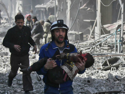 A Syrian civil defence member carries an injured child rescued from between the rubble of buildings following government bombing in the rebel-held town of Hamouria, in the besieged Eastern Ghouta region on the outskirts of the capital Damascus, on February 19, 2018. Heavy Syrian bombardment killed 44 civilians in rebel-held …