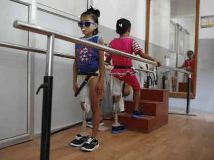 In this Oct. 16, 2015 photo, amputee victims in Nepal's massive 2015 earthquake, Nepalese girls Khendo Tamang, left, and Nirmala Pariyar, both 8, practice walking with new prosthetic legs at a clinic in Kathmandu, Nepal. Spending months together with surgeries and the following physical therapy, both girls were soon inseparable …