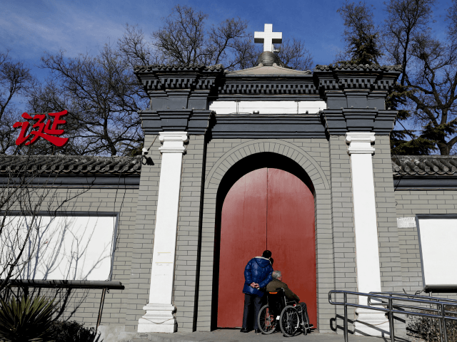 "A man peeks through a main entrance gate of the Nantang Catholic Church in Beijing, Wednesday, Dec. 28, 2016. China's head of religious affairs said that Beijing is willing to have constructive dialogue with the Vatican but stressed that Catholics should ""hold up high the flag of patriotism"" and adapt …"