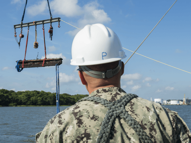 In a Friday, Aug. 14, 2015 photo provided by the US Navy, Chief Warrant Officer 3, Jason Potts, on scene commander for Task Element CSS Georgia, supervises as a piece of casemate, made of railroad ties and timber, which served as the outer layer of armor for CSS Georgia, is …