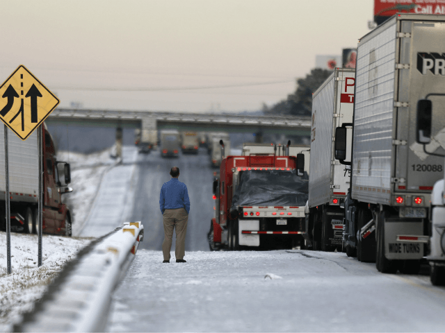 A man stands on the frozen roadway as he waits for traffic to clear along Interstate 75 Wednesday, Jan. 29, 2014, in Macon, Ga. A winter storm dumped snow and covered parts of the state with ice. Gov. Nathan Deal said early Wednesday that the National Guard was sending military …