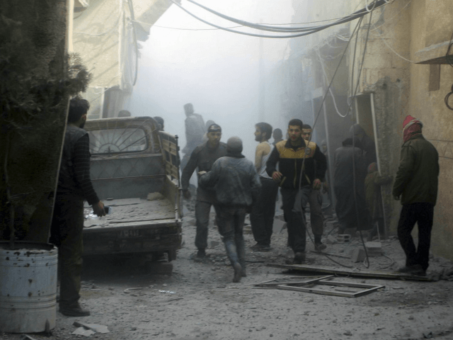 This photo released on Saturday, Feb 24, 2018 by the Syrian Civil Defense group known as the White Helmets, shows members of the Syrian Civil Defense group and civilians gathering to help survivors from a street attacked by airstrikes and shelling by Syrian government forces, in Ghouta, a suburb of …