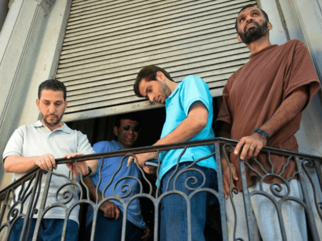 FILE - In this Dec. 12, 2014 file photo, former Guantanamo prisoners, from left, Adel bin Muhammad El Ouerghi from Tunisia, Ali Husain Shaaban from Syria, Ahmed Adnan Ajuri from Syria, and Palestinian Mohammed Abdullah Taha Mattan stand on a balcony of their temporary home in Montevideo, Uruguay. The men are four of six former prisoners who were held for 12 years at Guantanamo Bay. Uruguay's government has decided to extend for another year the economic aid that it has given the six former Guantanamo Bay prisoners who resettled in the country in 2014, officials said Thursday, Feb. 8, 2018. (AP Photo/Matilde Campodonico, File)