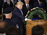 President Donald Trump touches the casket of Rev. Billy Graham as he lies in honor in the U.S. Capitol Rotunda, Wednesday, Feb. 28, 2018 in Washington. (Chip Somodevilla/Pool via AP)