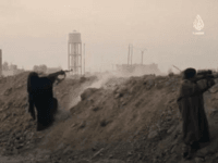 Female fighter: A woman dressed head to toe in black, including a burqa covering her face, fires an assault rifle as she fights for ISIS on the frontline