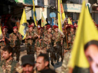 Kurdish People's Protection Units (YPG) military police members demonstrate with their flags and others bearing the portrait of Kurdistan Worker's Party (PKK) leader Abdullah Ocalan in the Kurdish town of Al-Muabbadah in the northeastern part of Hassakah province on February 24, 2018, denouncing the Turkish military operation against YPG forces …