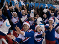 North Korean cheerleaders hold the flags of the unified Korean team during the women's preliminary round ice hockey match between Korea and Sweden, at the Ice Arena in Gangneung on February 12, 2018. / AFP PHOTO / Ed JONES (Photo credit should read ED JONES/AFP/Getty Images)