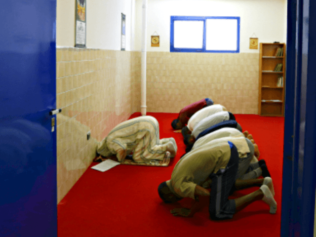 """In this photo taken on Friday, June 23, 2017, inmates pray with the Imam Mimoun El Hachmi, left, inside the Terni penitentiary, Italy. Stunned that Berlin market attack suspect spent time in Italian jails, Italy turns to """"moderate"""" imams to discourage radicalization among Muslim inmates. (AP Photo/Gregorio Borgia)"""