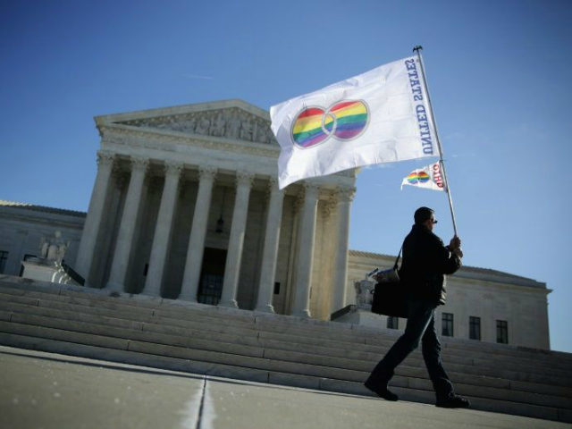 A demonstrator with a gay flag walks in front of the Supreme Court.
