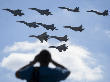 In this file photo taken on Saturday, Aug. 12, 2017 a man watches Russian military jets performing in Alabino, outside Moscow, Russia. The Russian military says major war games, the Zapad (West) 2017 maneuvers, set for next month will not threaten anyone. (AP Photo/Pavel Golovkin, File)