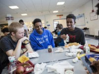 Abdiaziz Shaleh, right, a Lewiston high school senior and co-captain of the soccer team, and Essa Gedi, center, both whose families emigrated from Somalia, sit with classmate Isiah Leach, left, during lunch in the school's cafeteria in Lewiston, Maine, Wednesday, March 15, 2017. Two years ago, immigrant children led the …