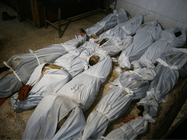 The bodies of civilians who were killed in Syrian army bombardment on the town of Hamouria in the rebel-held enclave of Eastern Ghouta are seen lying on the ground at a make-shift morgue the morning after the attacks on February 20, 2018. / AFP PHOTO / ABDULMONAM EASSA (Photo credit …