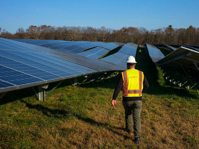 GRAFTON, MASSACHUSETTS - DECEMBER 4: Employees from a Radian Generation's operations and maintenance team change out a faulty solar inverter along a row of solar panels December 4, 2017 at the family-owned Knowlton Farm in Grafton, Massachusetts. The 3.7 megawatt solar array is owned and operated by BlueWave Solar which …