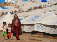 Syrian internally displaced people walk in the Atme camp, along the Turkish border in the northwestern Syrian province of Idlib, on March 19, 2013. The conflict in Syria between rebel forces and pro-government troops has killed at least 70,000 people, and forced more than one million Syrians to seek refuge …