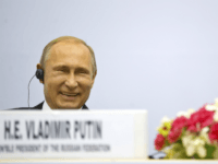 Russian President Vladimir Putin share a laugh as they attend a session of the World Diamond Conference in New Delhi, India, Thursday, Dec. 11, 2014. Putin was holding talks with Indian leaders Thursday to strengthen trade and energy cooperation with Asia's third-largest economy as Western sanctions threaten to push his country's economy to the brink of a recession. (AP Photo/ Saurabh Das)