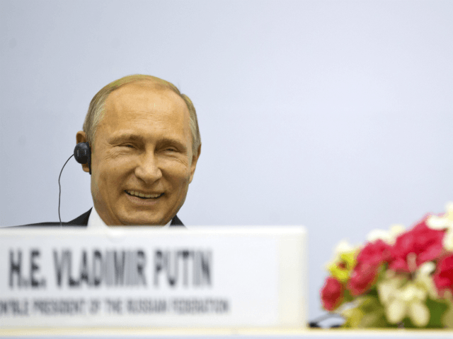 Russian President Vladimir Putin share a laugh as they attend a session of the World Diamond Conference in New Delhi, India, Thursday, Dec. 11, 2014. Putin was holding talks with Indian leaders Thursday to strengthen trade and energy cooperation with Asia's third-largest economy as Western sanctions threaten to push his …