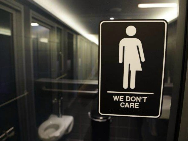 In this Thursday, May 12, 2016 file photo, signage is seen outside a restroom at 21c Museum Hotel in Durham, N.C. Ten states sued the federal government Friday, July 8, 2016 over rules requiring public schools to allow transgender students to use restrooms conforming to their gender identity, joining a …