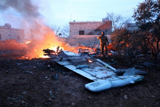 A rebel fighter takes a picture of a downed Sukhoi-25 fighter jet in Syria's northwest province of Idlib
