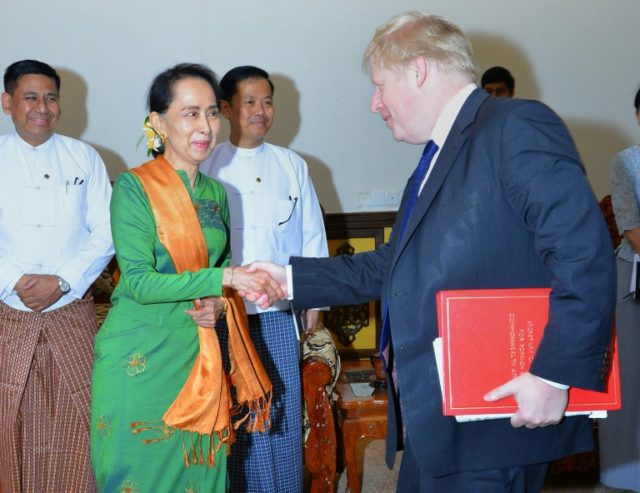 Myanmar State Counsellor Aung San Suu Kyi (L) shakes hands with Britain's Foreign Minister Boris Johnson at the start of their meeting in Naypyidaw, in a photo taken and released on February 11, 2018 by Myanmar's Ministry of Information