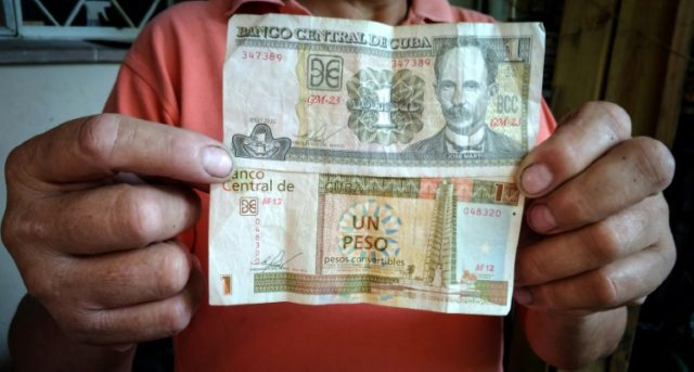 A Cuban worker holds bills for a Cuban peso (top) and a Cuban convertible peso (bottom) in Havana