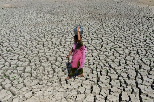 A woman searching for water walks on the parched bed of Chandola Lake, near the Indian city of Ahmedabad. A severe drought struck the region in 2016