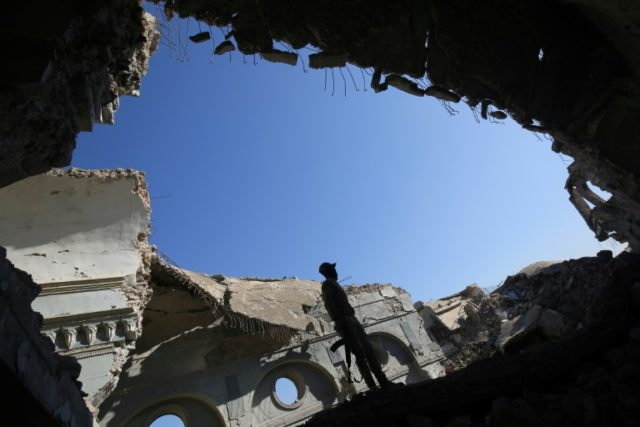 A fighter stands on debris at a destroyed church in the Iraqi city of Mosul on January 9, 2018