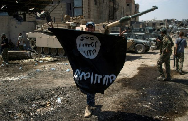 A member of the Iraqi forces holds the Islamic State group flag upside down in Mosul on July 1, 2017