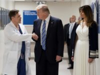 US President Donald Trump shakes hands with doctor Igor Nichiporenko (L) at Broward Health North hospital with First Lady Melania Trump at his side as he pays his respects following the Florida school shooting