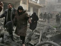 Civilians flee the rebel-held Syrian town of Saqba, in the besieged Eastern Ghouta region outside Damascus, after a reported Assad regime air strike