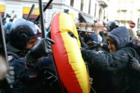 Police officers in riot gear grapple with anti-fascist protesters at a rally in Milan on Saturday